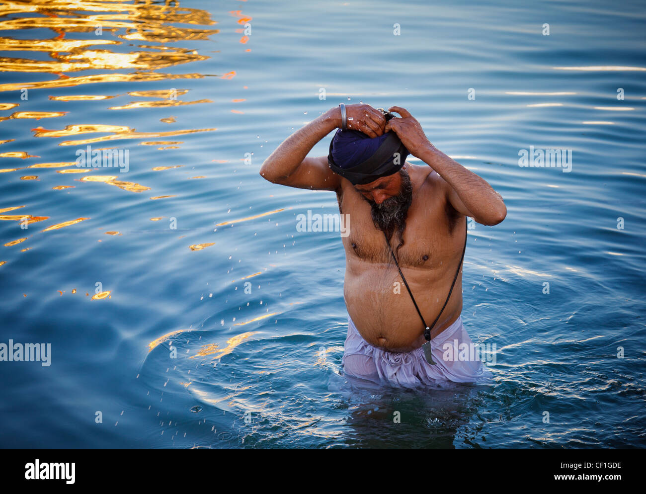 Un uomo Sikh prende un bagno in Amrit Sarovar, la piscina che circonda il tempio d'oro di Amritsar Punjab, India Foto Stock