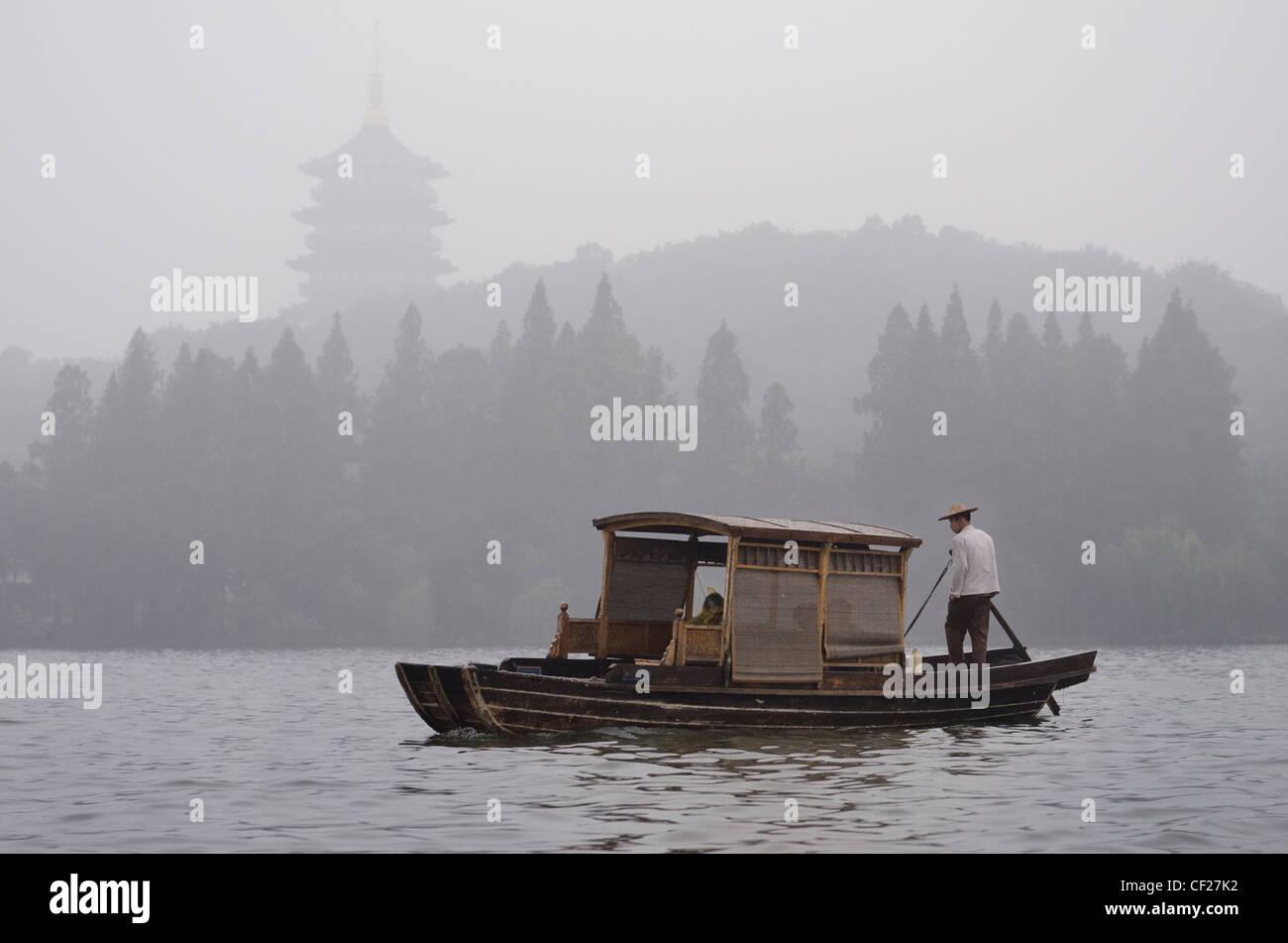 Crociera in barca con vogatore sotto la pioggia con la pagoda leifeng sul West Lake hangzhou cina Immagini Stock