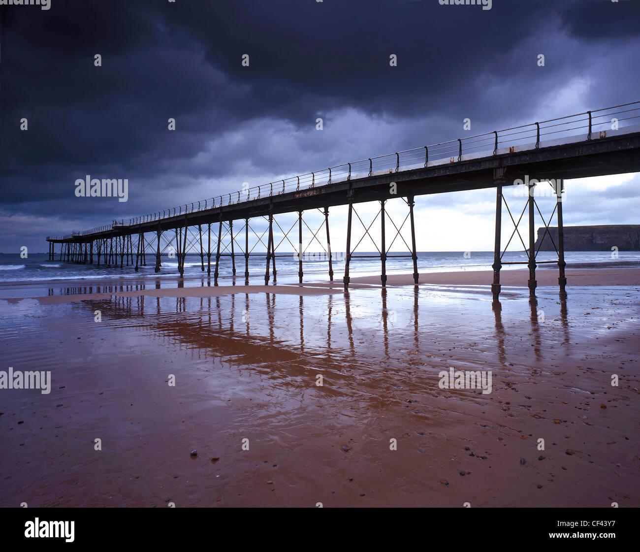 Saltburn Pier, l'ultimo pier rimanendo nello Yorkshire, con la bassa marea come aria di tempesta overhead. Immagini Stock