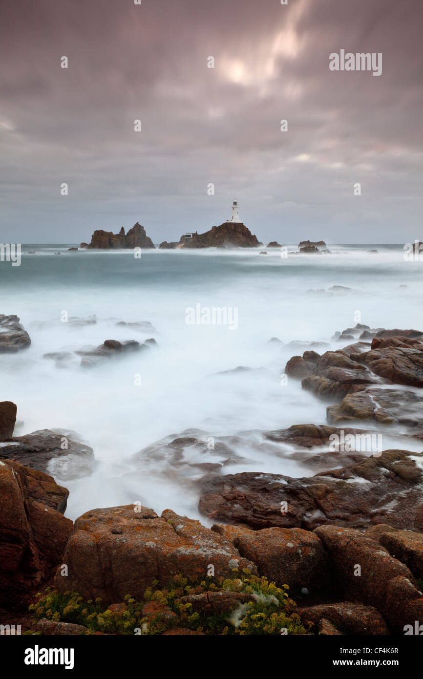 Mare mosso circa la Corbiere Lighthouse al tramonto. Il faro è stato il primo nelle isole britanniche per essere Immagini Stock