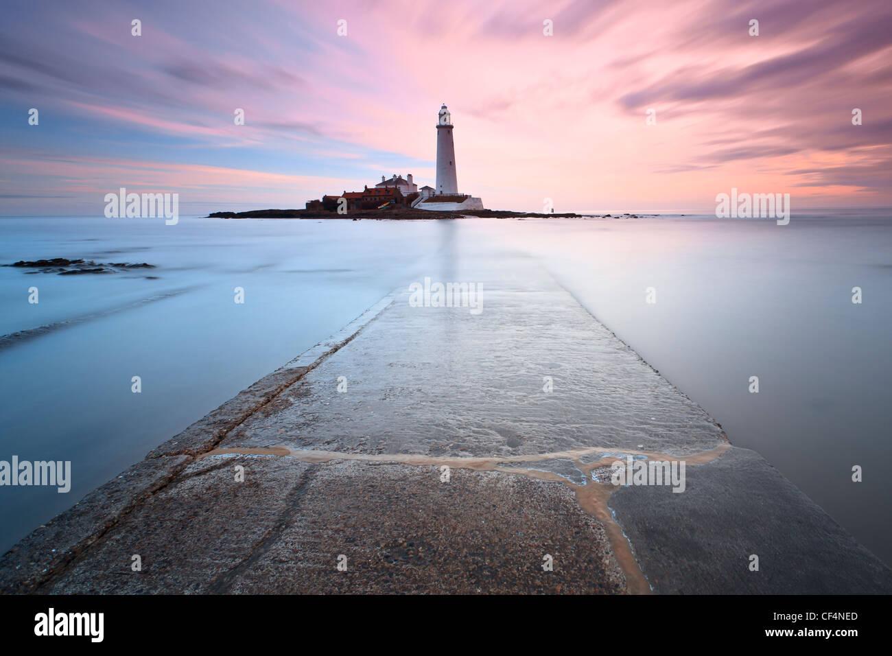 Vista lungo la parte sommersa causeway concrete che portano a St Mary's Lighthouse vicino a Whitley Bay a sunrise. Immagini Stock