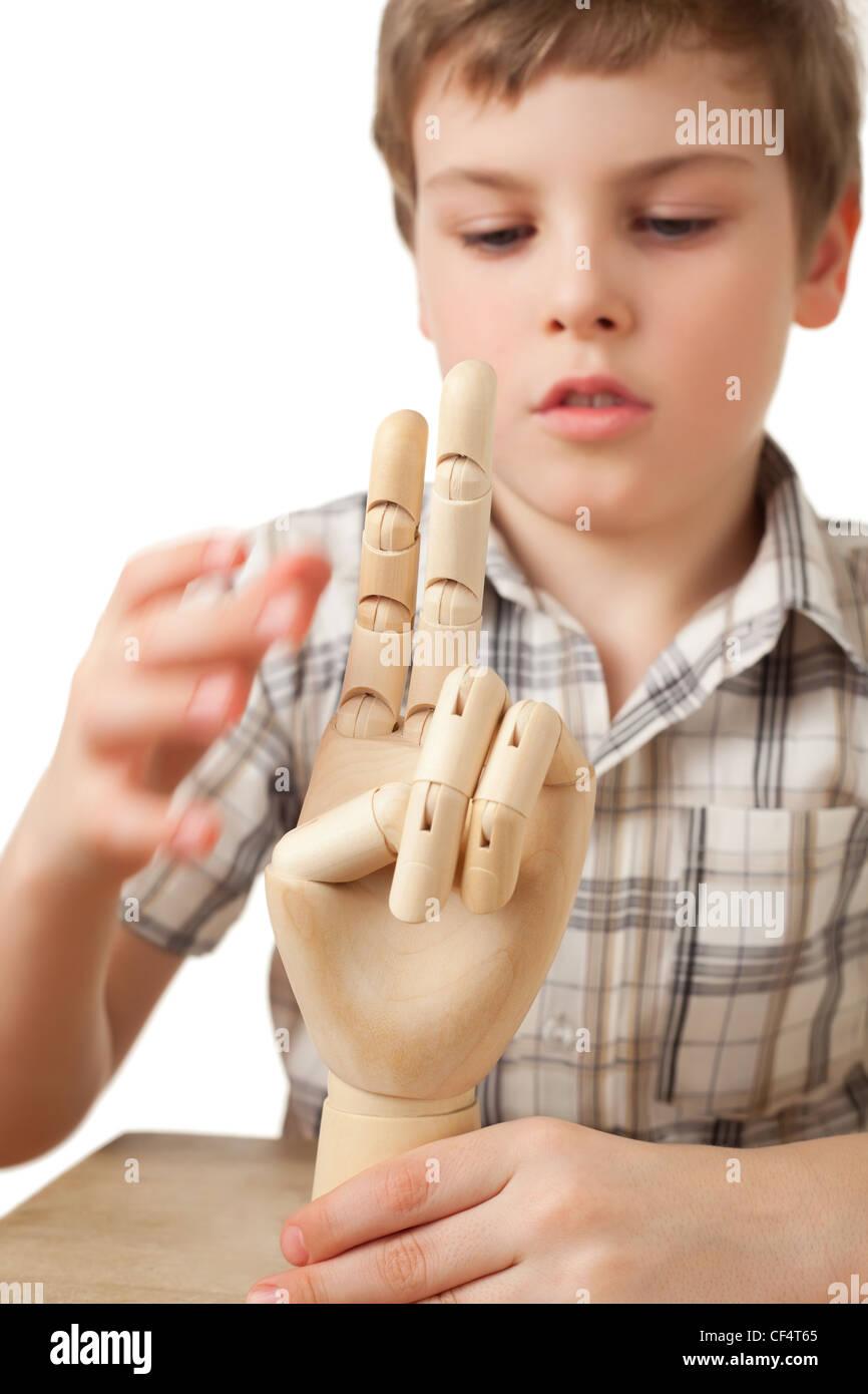Il ragazzo è giocato dalla mano di legno del manichino isolati su sfondo bianco Immagini Stock