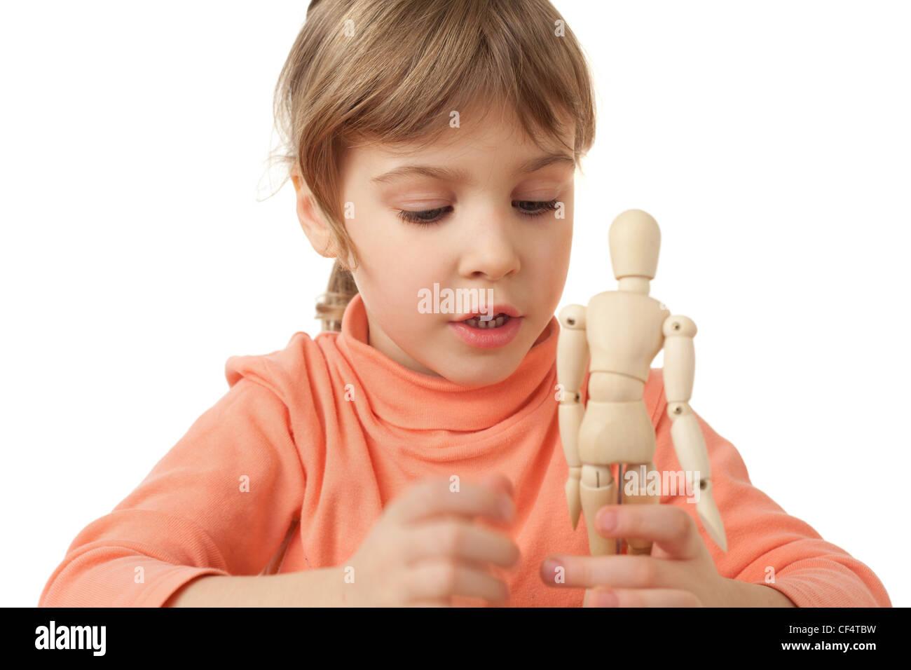 Graziosa bambina è svolto dal legno manichino poco isolato su sfondo bianco Immagini Stock