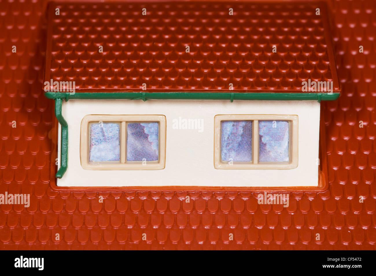 Attico sul tetto del giocattolo casa di plastica,due finestre Immagini Stock