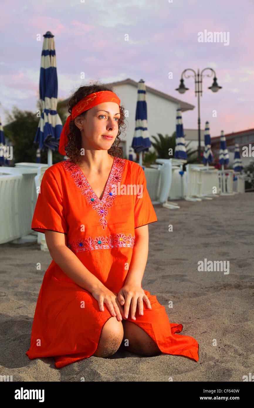 faaf1a540898 Bella giovane donna vestita in abito rosso seduto sulla spiaggia di sera  Immagini Stock