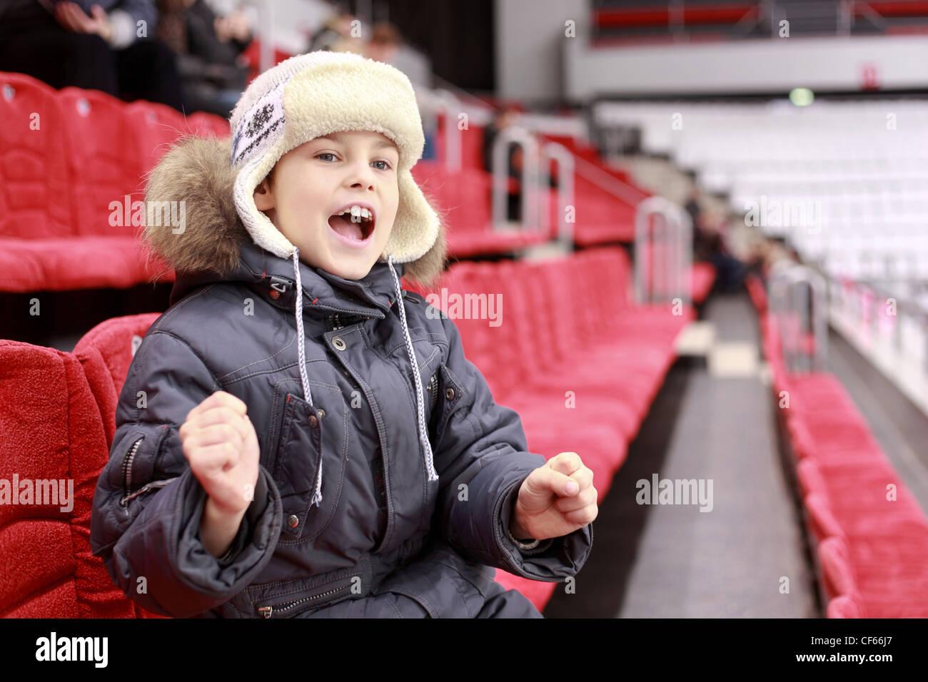 Ragazzo ad alta voce grida sulla partita di hockey su ghiaccio Immagini Stock