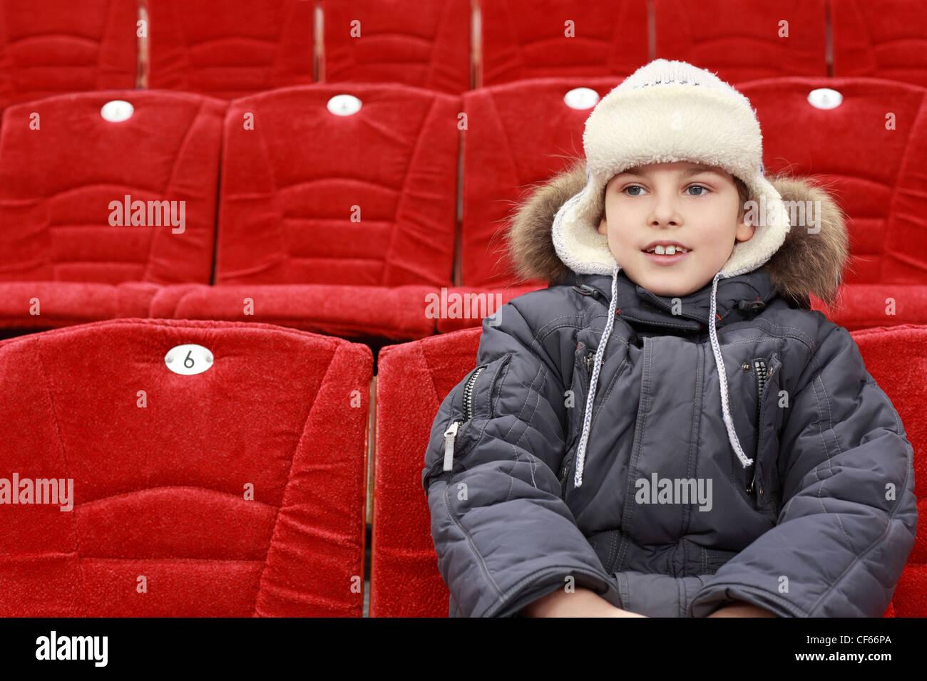 Il ragazzo si siede in attesa della partita di hockey su ghiaccio Immagini Stock