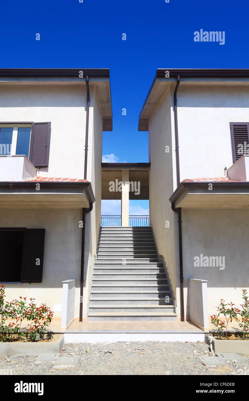 Case A Due Piani scale tra i due in cemento bianco a due piani di case con