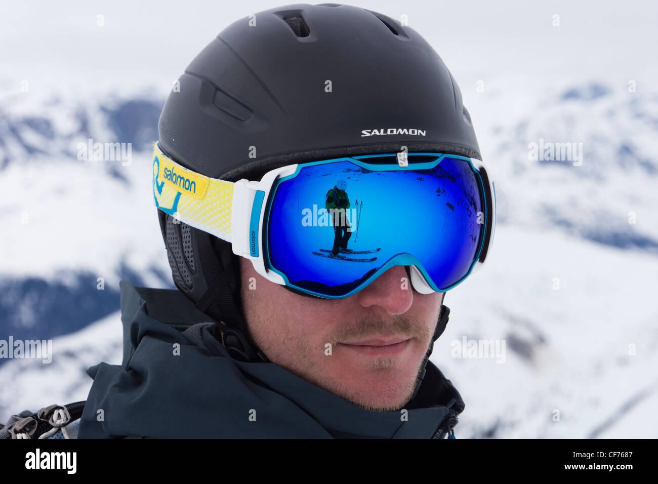 Uomo che indossa un Salomon sci casco con uno sciatore sulla neve si riflette in una coppia di blu occhiali da sci Immagini Stock