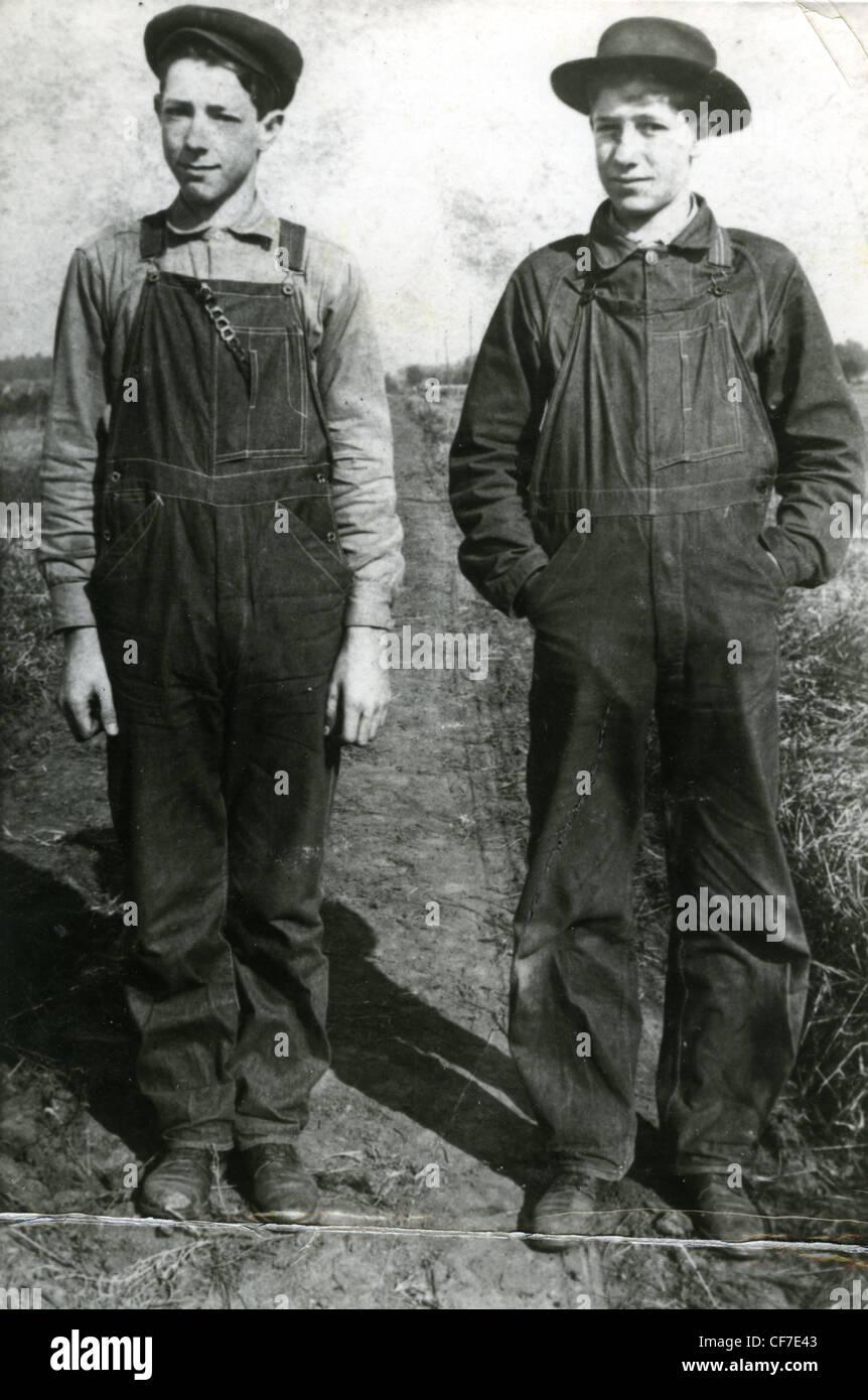 Fattoria di due ragazzi in tuta di stand per un ritratto in un campo durante gli anni venti o trenta grande depressione Immagini Stock