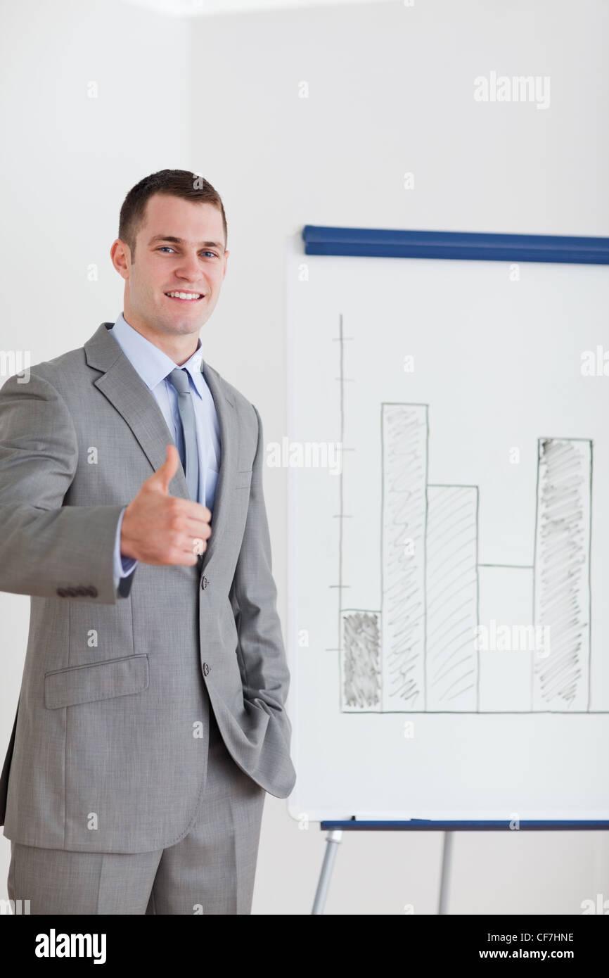 Imprenditore dando pollice in alto accanto al grafico a colonna Immagini Stock