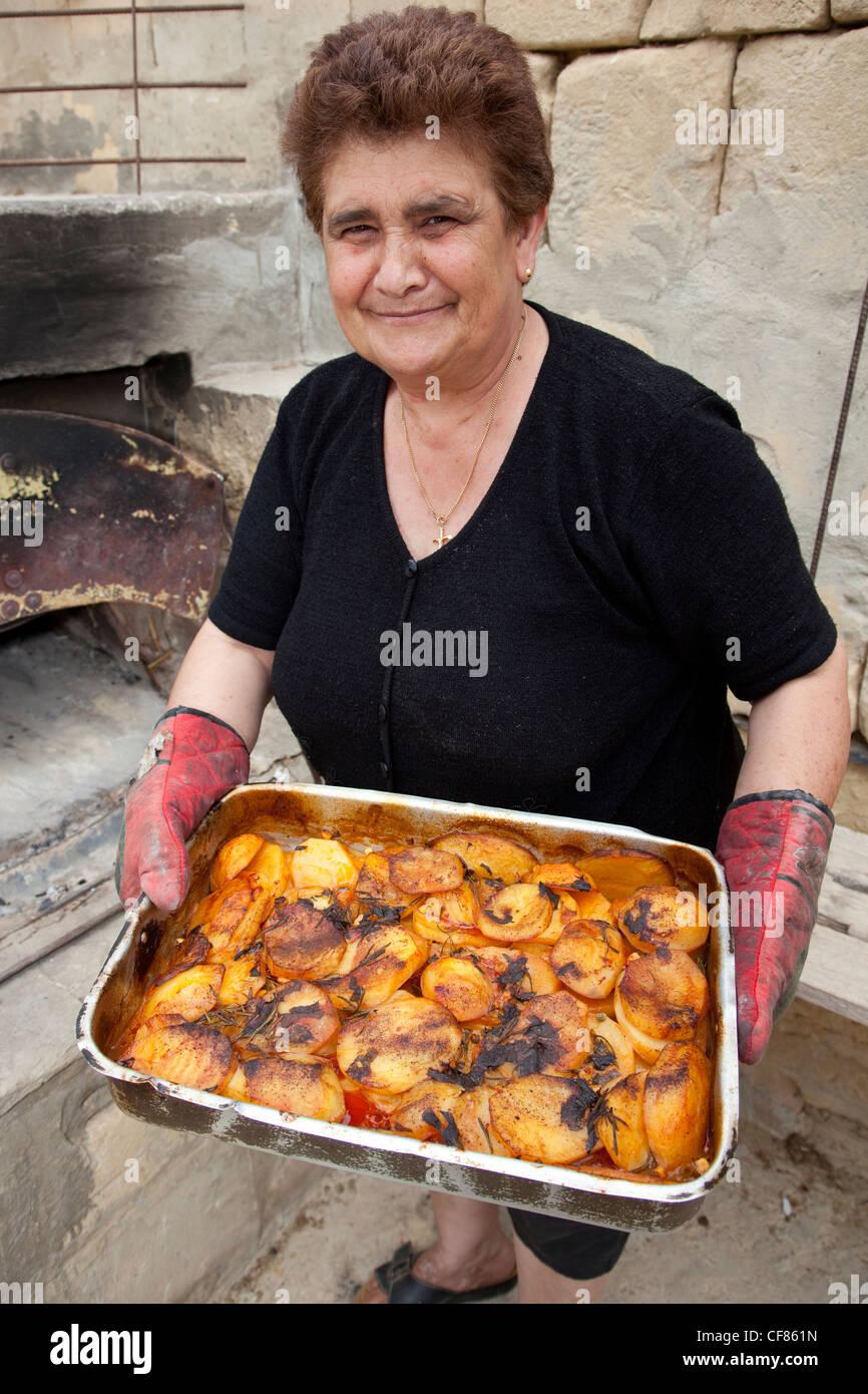 Una vecchia donna di Gozo tenendo fuori un piatto di patate arrosto da un forno costruire nel suo cortile nel casale. Immagini Stock