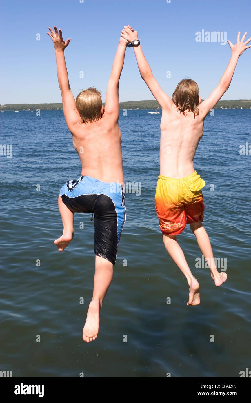 Due ragazzi (9 & 12 anni) salta fuori da dock nel lago, Sylvan Lake, Alberta, Canada. Immagini Stock