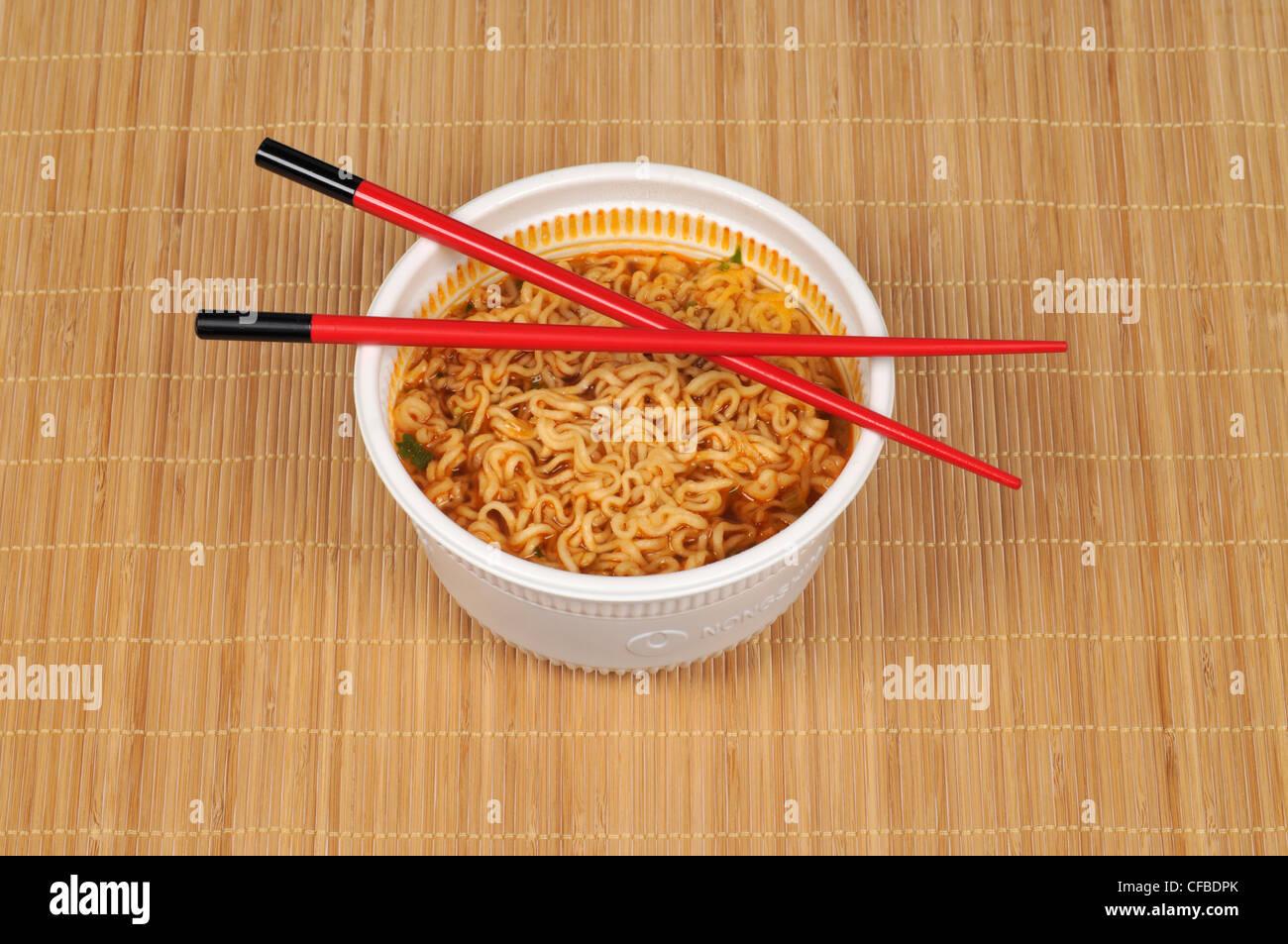 Ciotola di spaghetti orientali con bacchette sul tappetino di bambù Immagini Stock