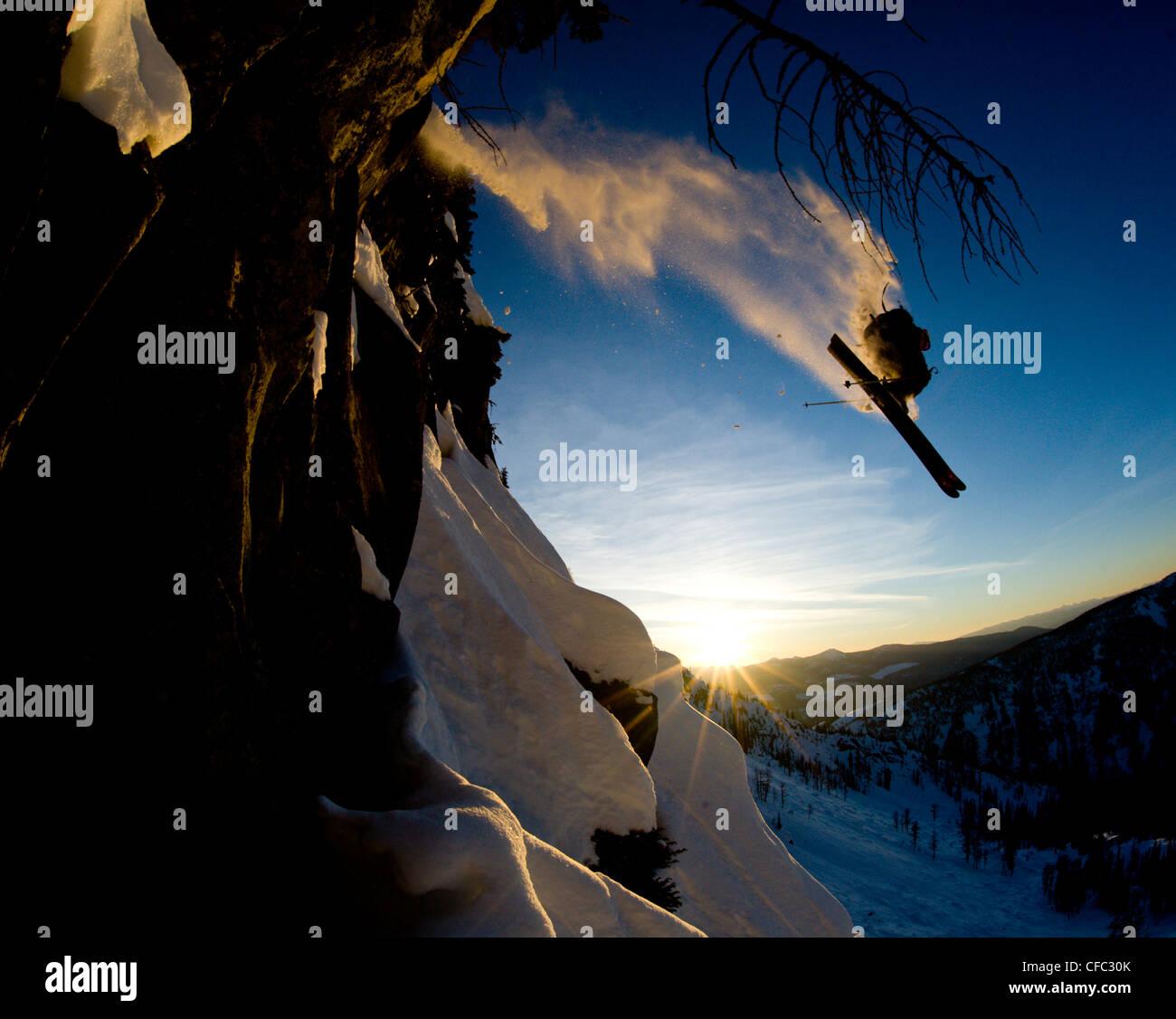 Un giovane maschio sciatore prende aria enorme da un dirupo nel backcountry vicino a Whitewater Resort invernale, Immagini Stock