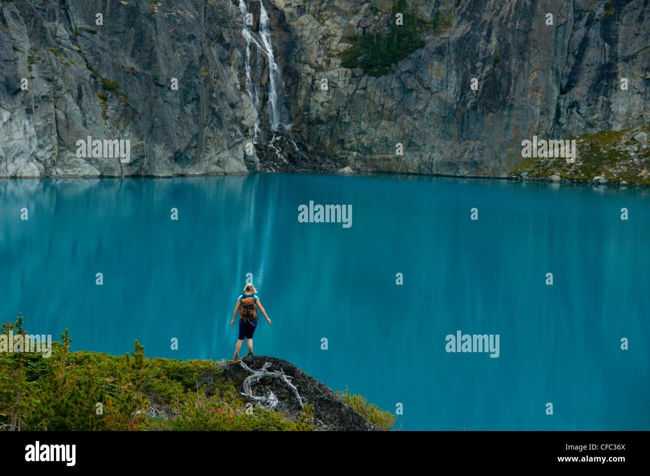 Una giovane donna escursioni nella parte anteriore di un lago azzurro e cascata nella gamma Niut, British Columbia, Immagini Stock