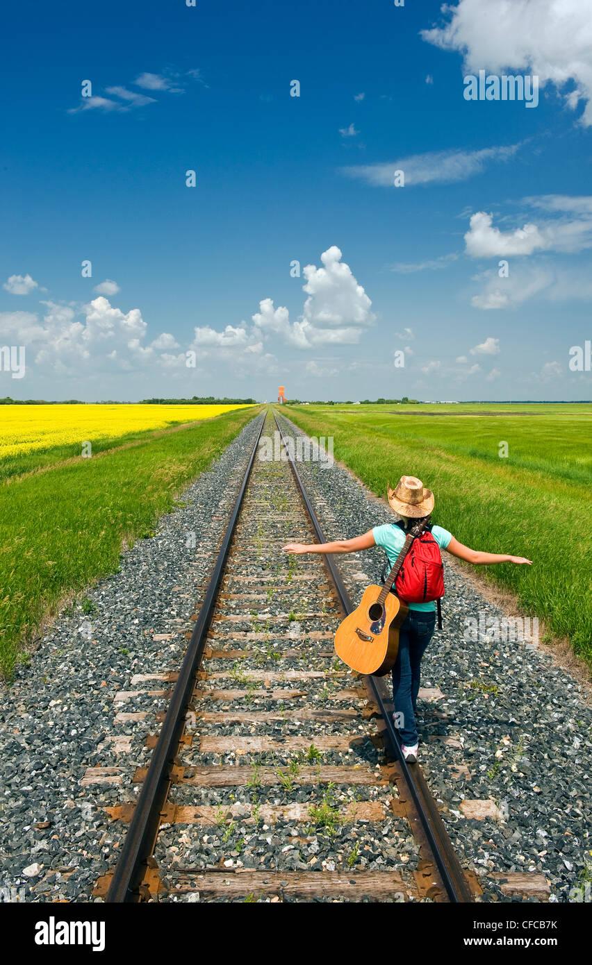 18 anni di chitarra ragazza camminare lungo la ferrovia Immagini Stock