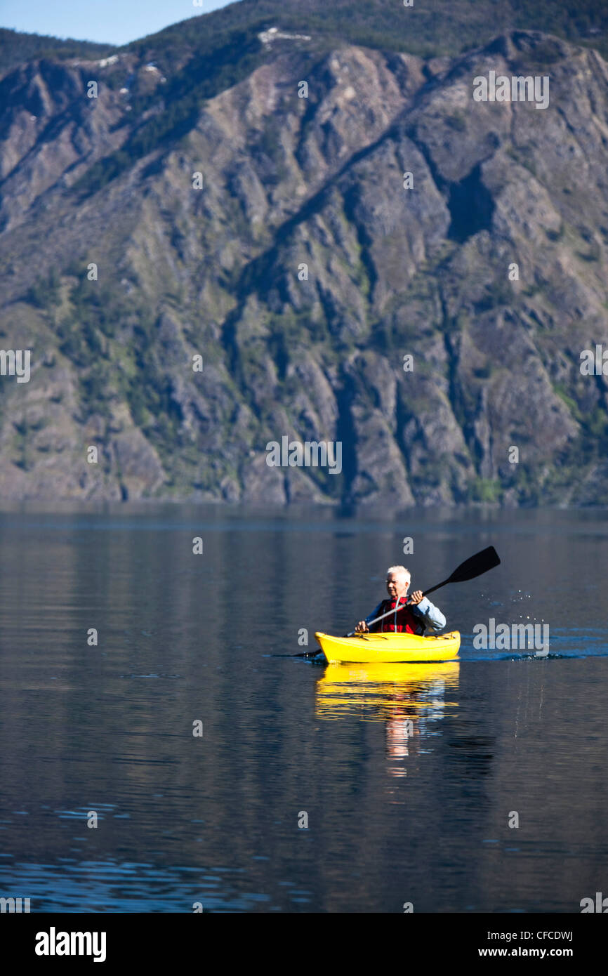 Un avventuroso ritirò man kayak attraverso un enorme lago calmo in Idaho. Immagini Stock