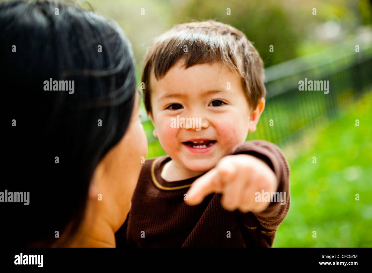 Una madre trattiene e bacia il figlio di 2 anni. Immagini Stock