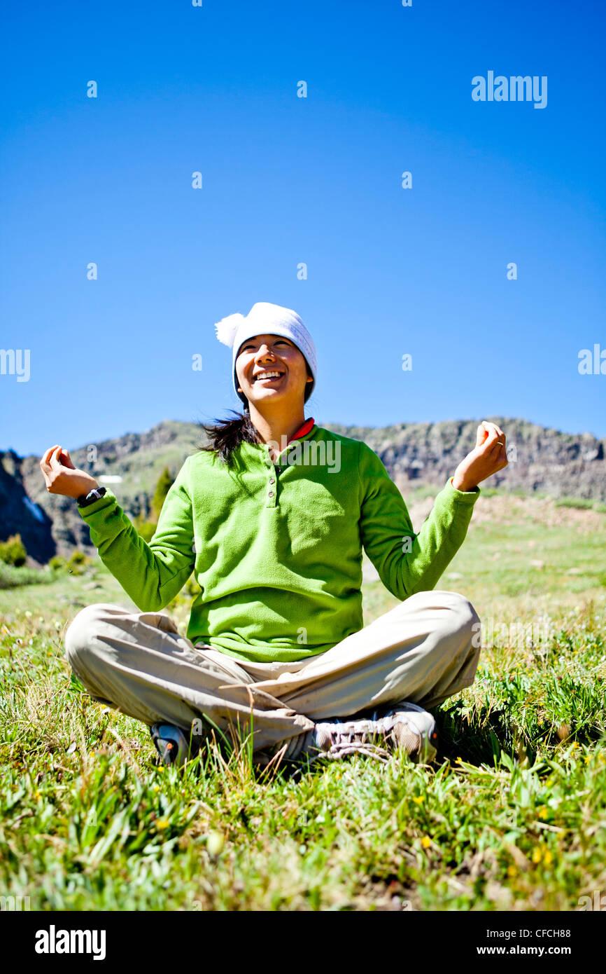 Una donna sorrisi come siede zampe trasversale in un prato con fiori selvaggi facendo un Buddha pongono. Sono appena Immagini Stock