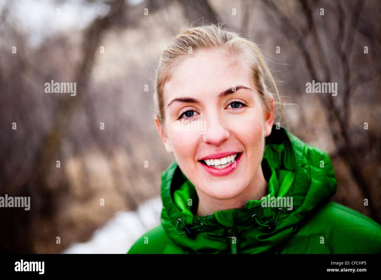 Una giovane donna corre un lungo coperto di neve sentiero sterrato attraverso sfrondato di alberi decidui appena Immagini Stock