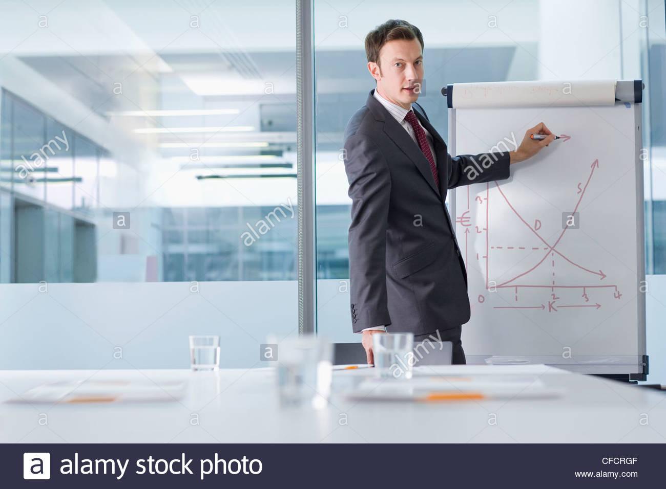 Ritratto di imprenditore in tuta di puntamento grafico in sala conferenze Immagini Stock