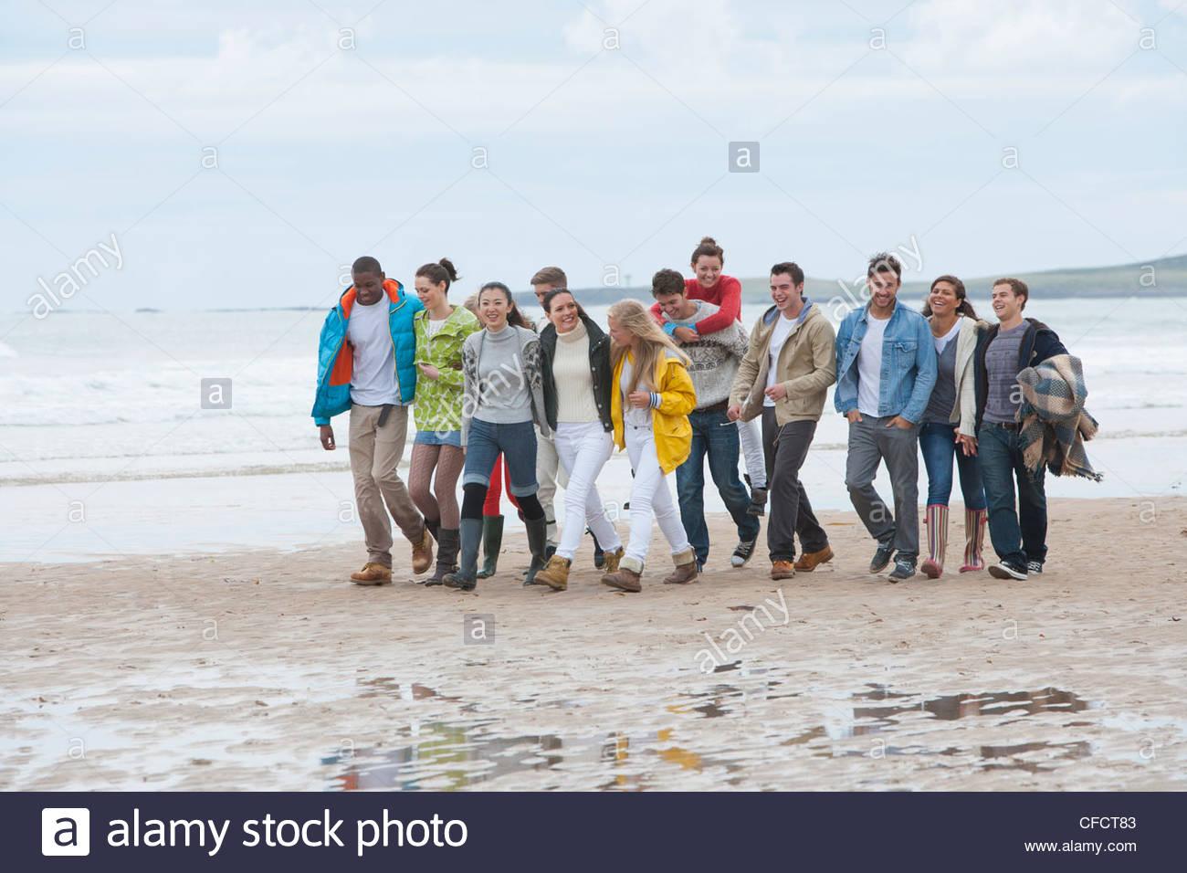 Grande gruppo di amici a piedi sulla spiaggia Immagini Stock