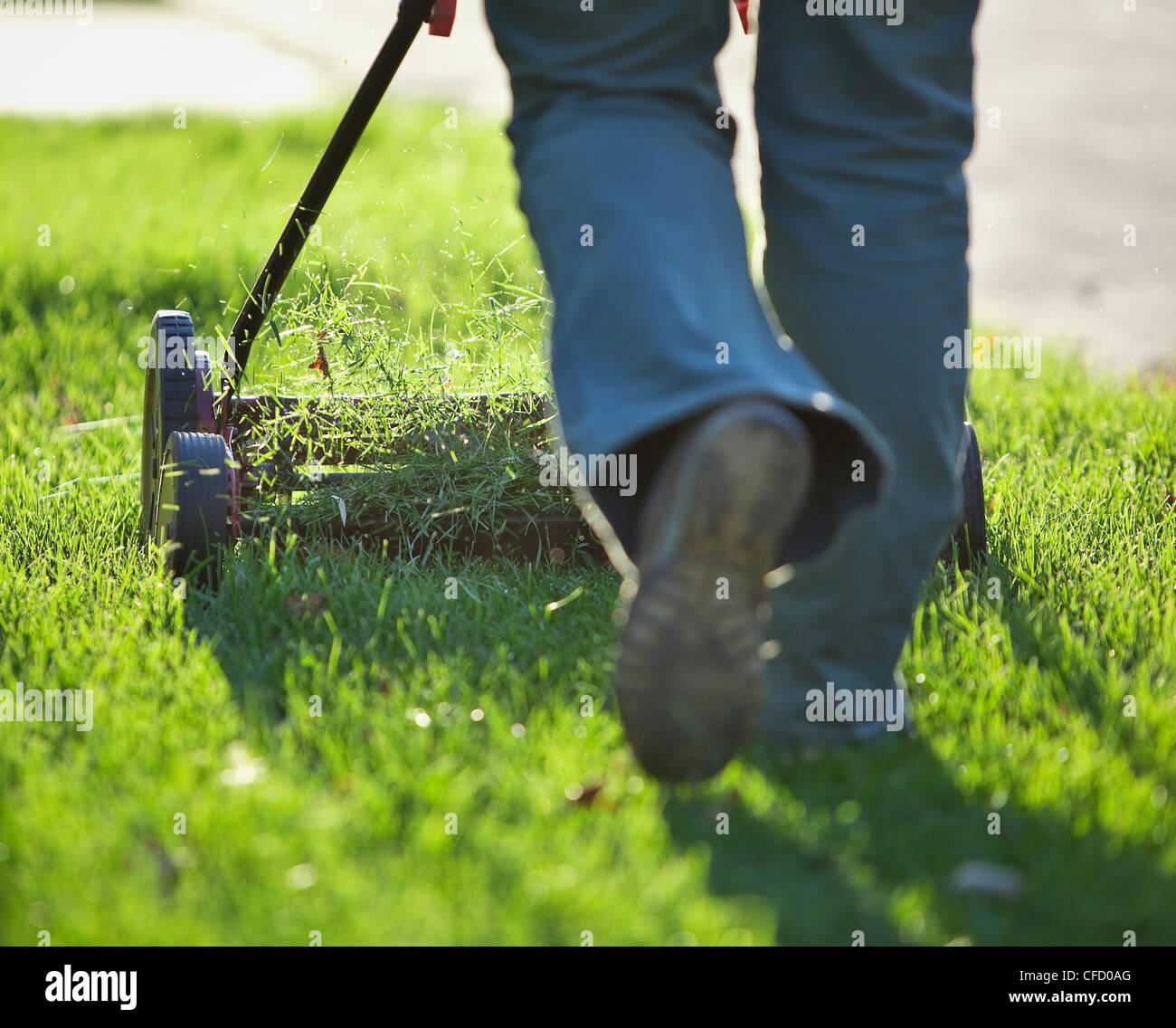 Donna taglio erba con rispettosa dell'ambiente tosaerba. Winnipeg, Manitoba, Canada. Immagini Stock