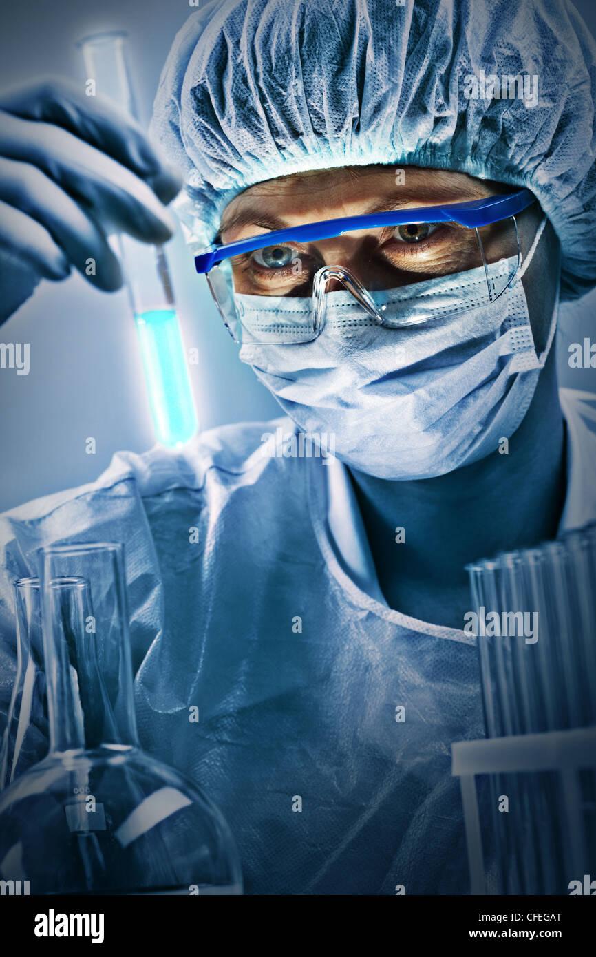 Colpo verticale della donna in occhiali ed uniforme guardando un tubo con il campione testato Immagini Stock