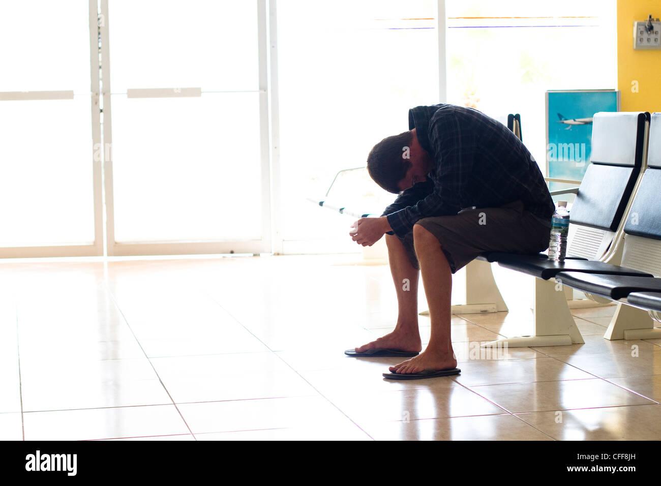Un esausto viaggiatore maschio attende nel terminal di un aeroporto per il volo per arrivare a Manzanillo International Immagini Stock