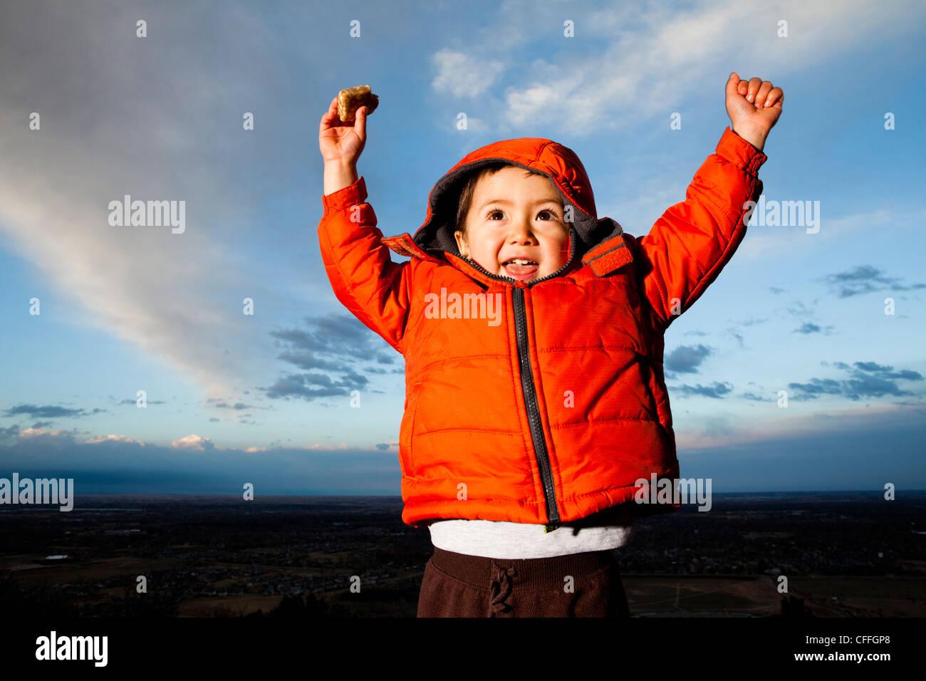 Un giovane ragazzo alza le mani in eccitazione all'aperto in Fort Collins, Colorado. Immagini Stock