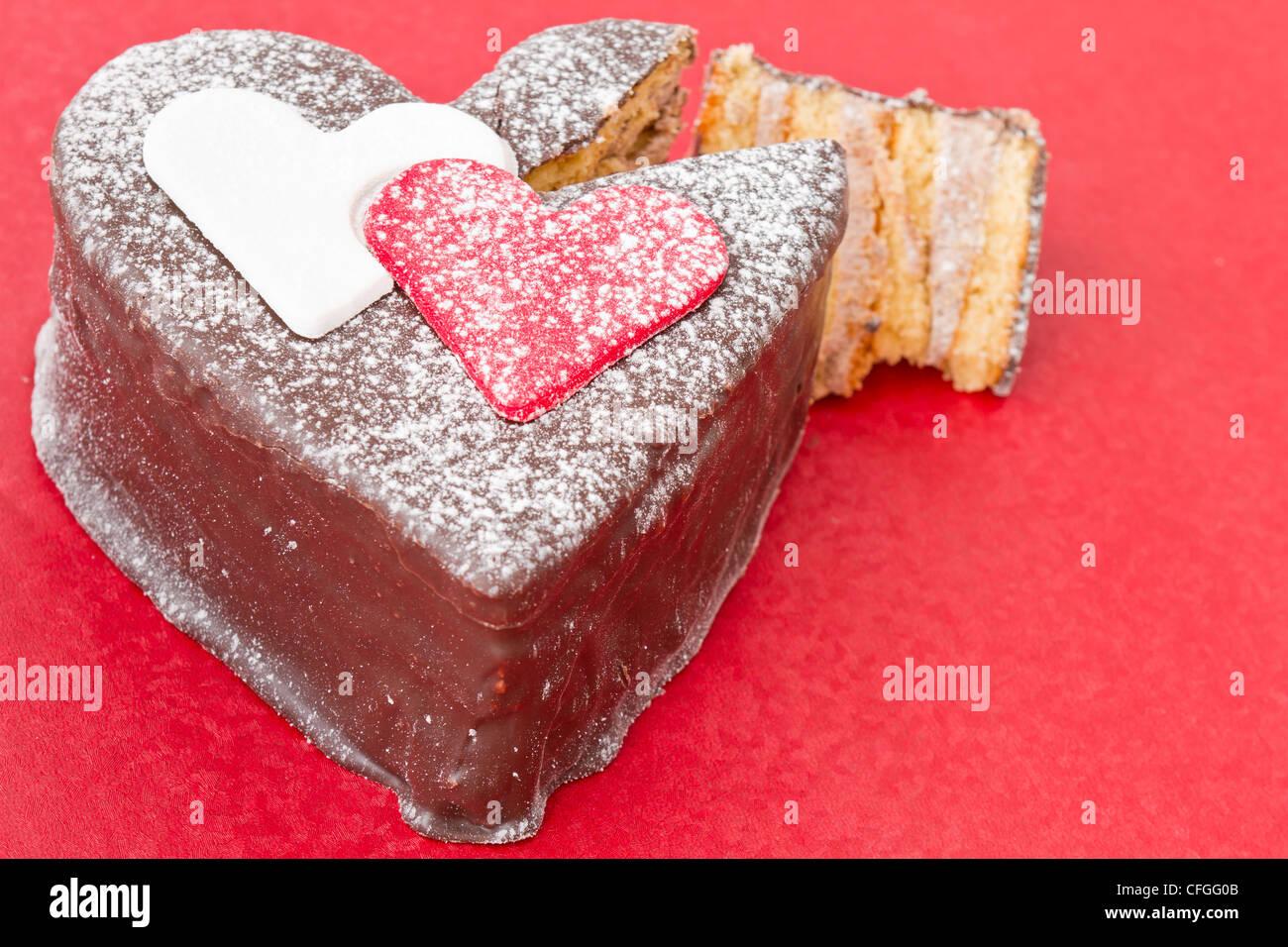 A forma di cuore ad slice di un cioccolato-torta sul tavolo rosso Immagini Stock