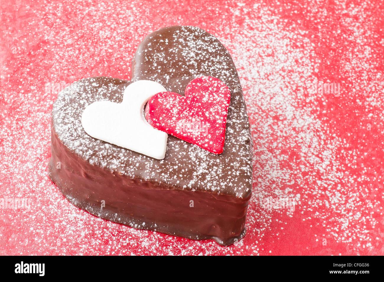 A forma di cuore ad fetta di un cioccolato torta-su sfondo rosso Immagini Stock