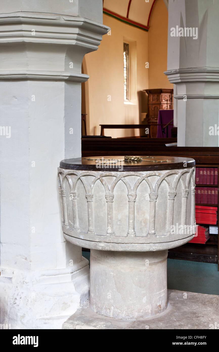 """Norman font in tutti i santi della Chiesa"""", una tipica C di e villaggio inglese chiesa in Lydiard Millicent,Swindon, Immagini Stock"""