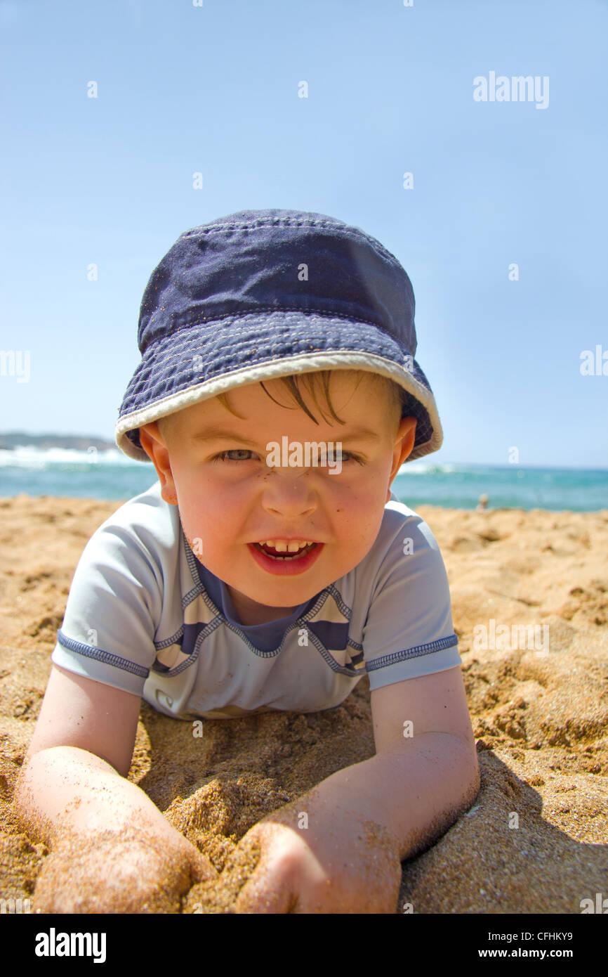 Felice ragazzo disteso di sabbia su una spiaggia che indossa un cappello per  il sole 56c9ddd33a6e