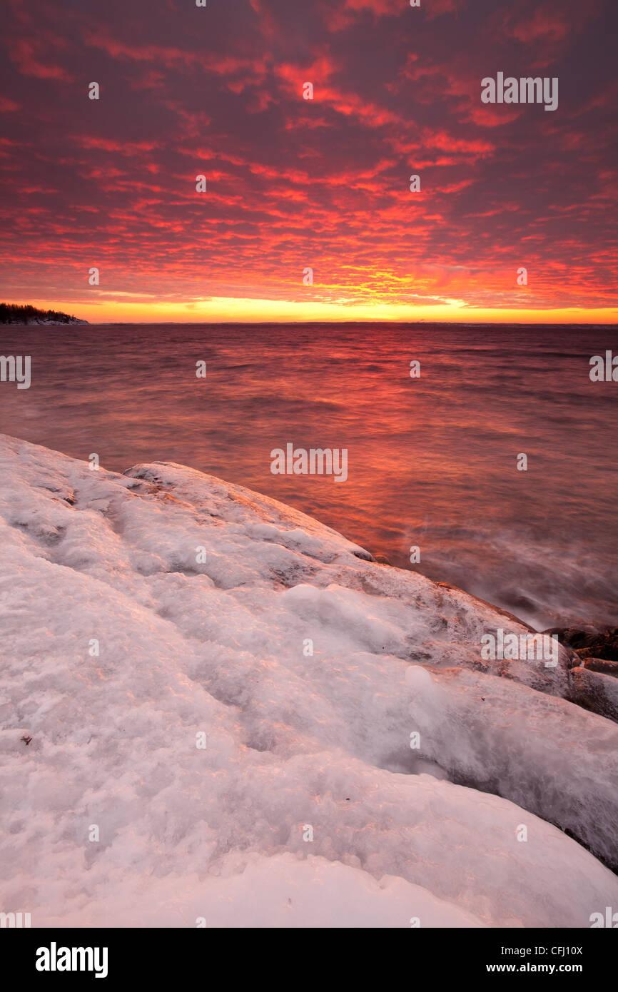 Icy costa e colorato il cielo al tramonto a Larkollen in Rygge, Østfold fylke, Norvegia. Foto Stock