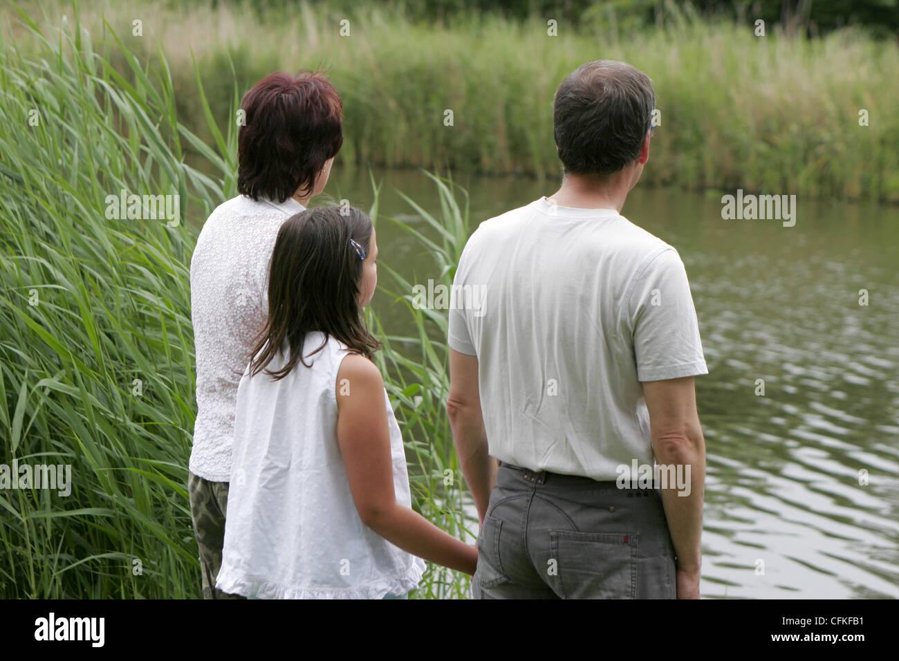 Vista posteriore dei genitori e un solo bambino per mano e contemplativo a lato dell'acqua. Immagini Stock