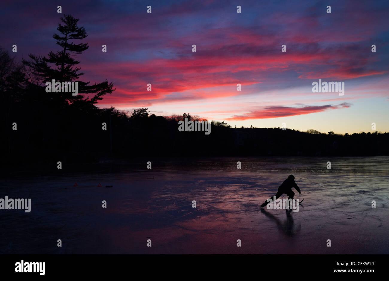 Un capretto pattini durante la pratica di hockey su congelati Lago di cioccolato a Halifax, Nova Scotia, Canada, Immagini Stock