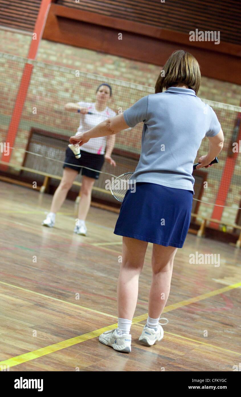 Due donne riproduzione di badminton al loro club locale, Newmarket Suffolk REGNO UNITO Immagini Stock