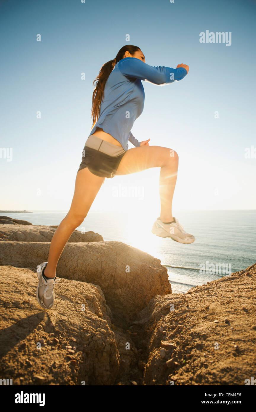Stati Uniti, California, San Diego, Donna jogging lungo la costa del mare Immagini Stock