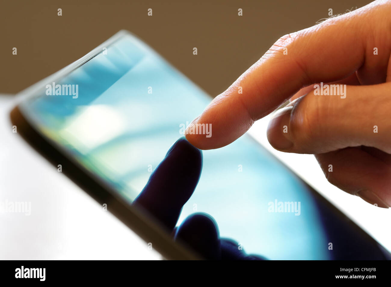 Dito toccando schermo di una tavoletta digitale Foto Stock