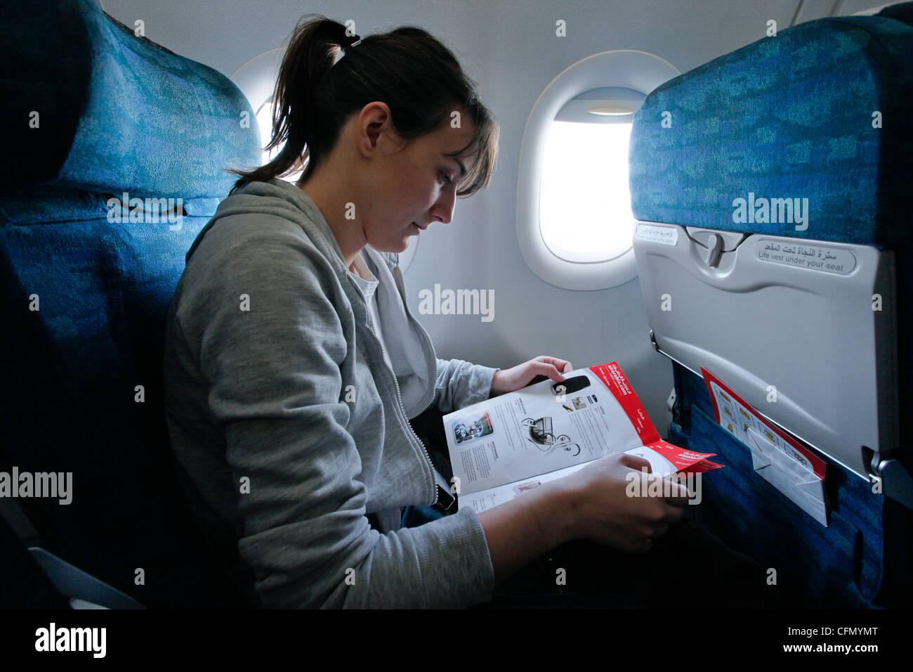 Una giovane donna legge un catalogo durante un volo Immagini Stock