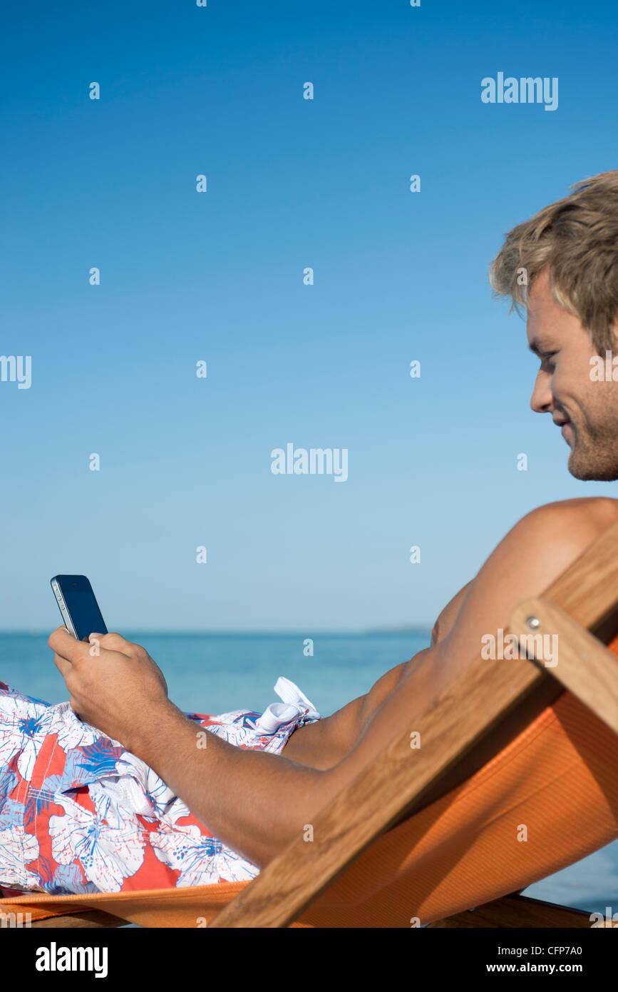 Giovane uomo per la messaggistica di testo a beach Immagini Stock