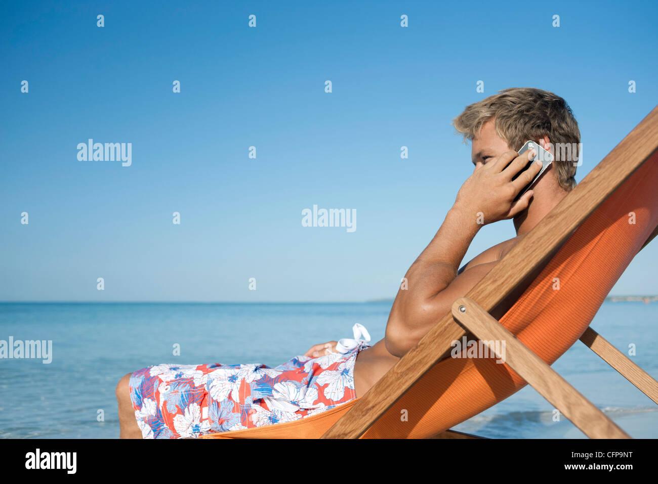 Giovane uomo parlando al cellulare in spiaggia Immagini Stock