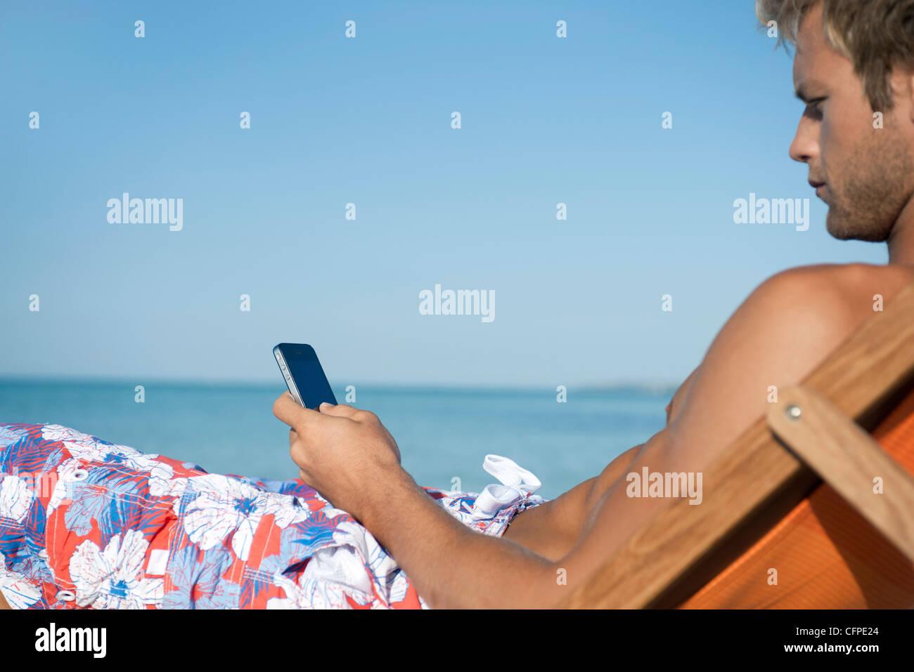Giovane uomo per la messaggistica di testo sulla spiaggia Immagini Stock