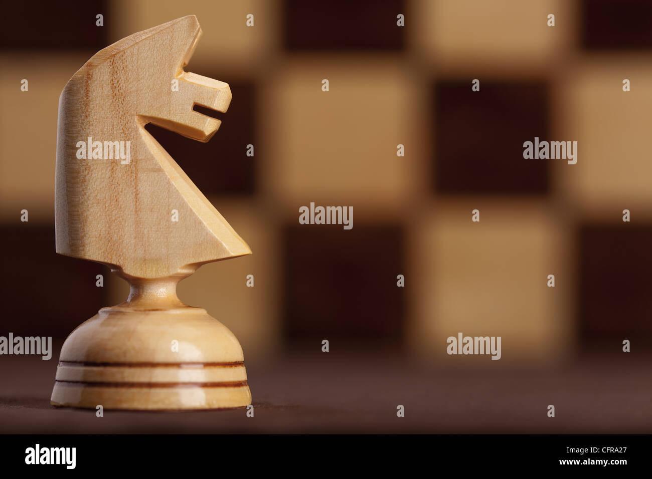 Legno cavaliere bianco su sfondo a scacchiera Immagini Stock