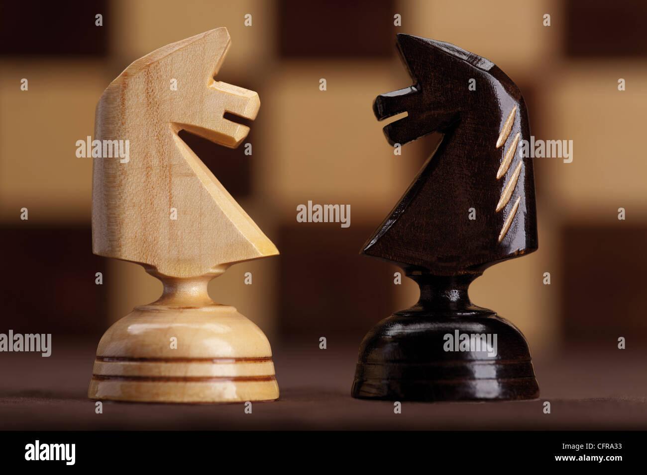 Bianco e cavalieri neri su sfondo a scacchiera Immagini Stock