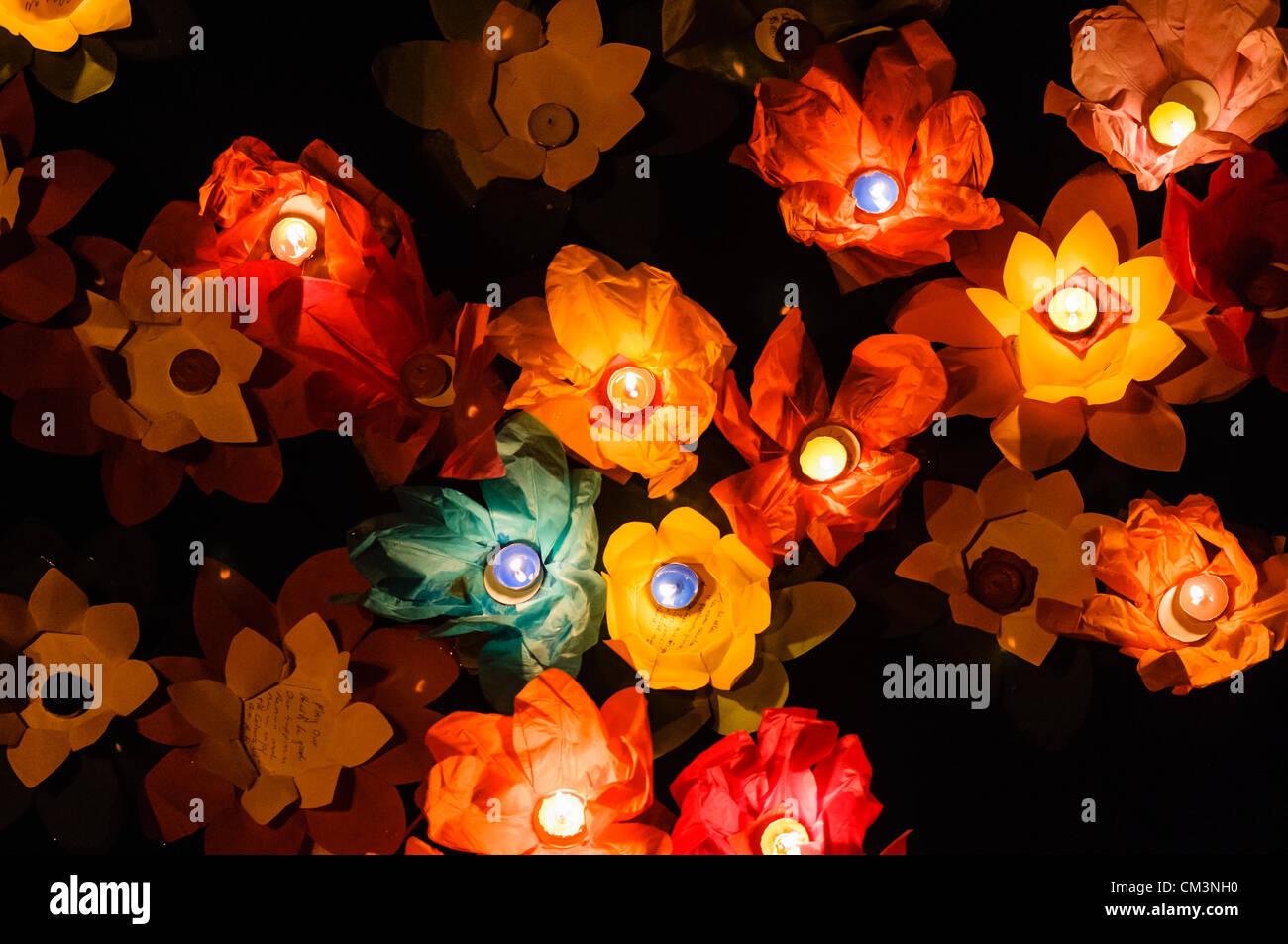 Carta fiori di loto con candele galleggiante sulle rive di un fiume di notte per contrassegnare i cinesi Mid-Autumn Foto Stock