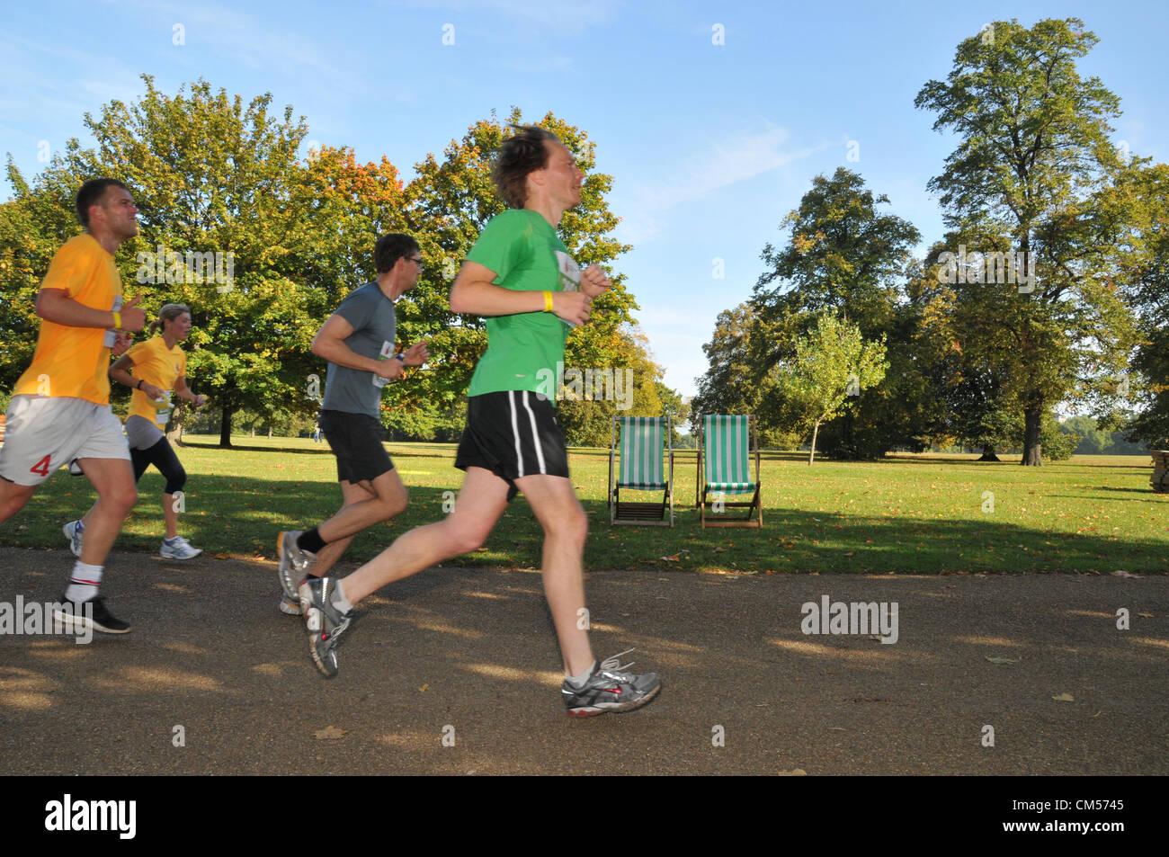 Hyde Park, London, Regno Unito. Il 7 ottobre 2012. I corridori passare empty sdraio come fanno il loro modo attraverso Immagini Stock