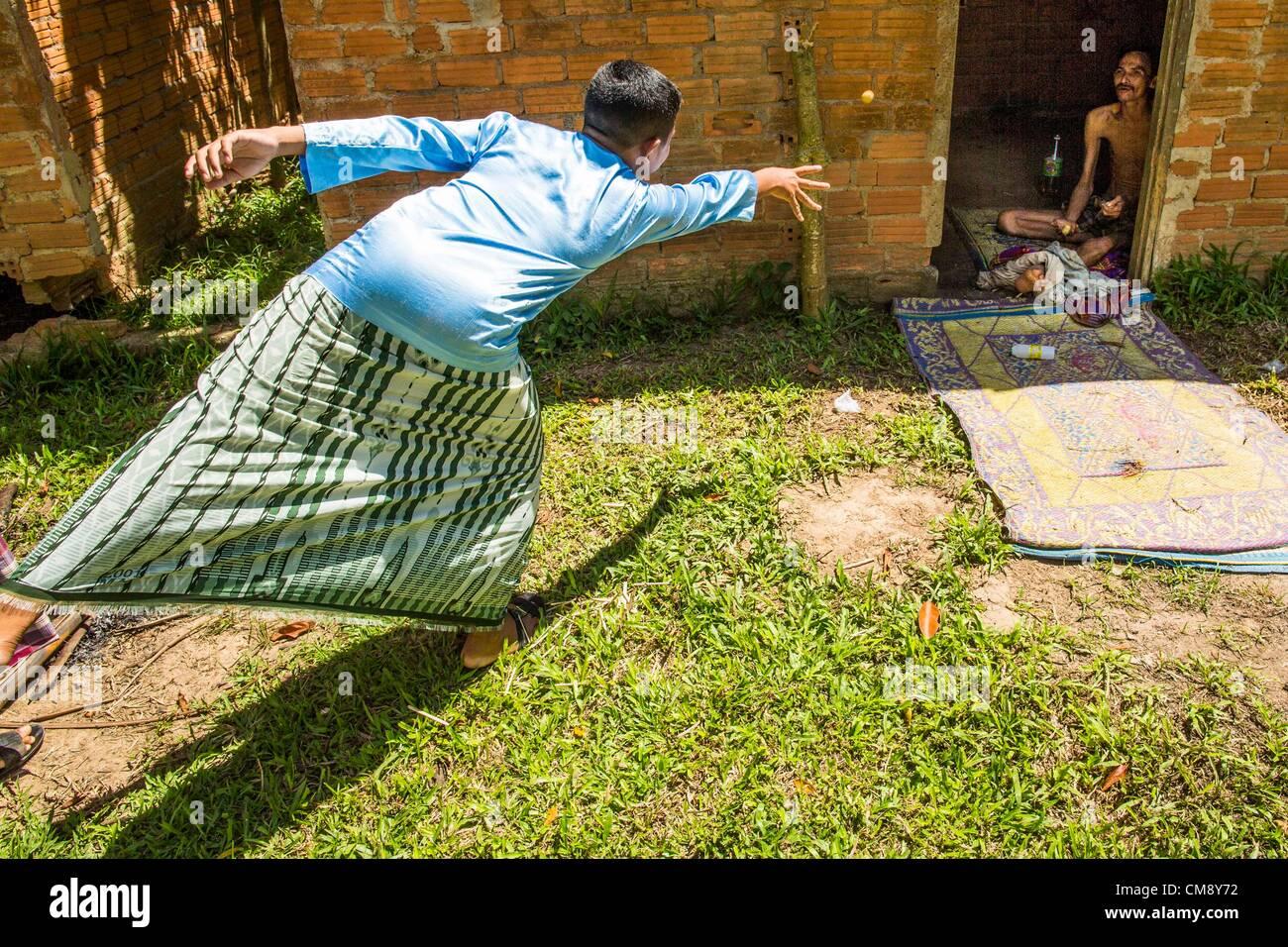 Ottobre 29, 2012 - Mayo, Pattani, Tailandia - un quartiere boy getta frutto di un paziente presso il Bukit Kong Immagini Stock